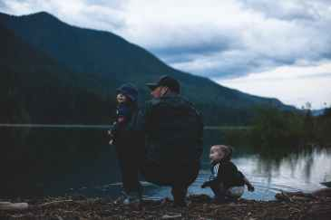 man with two kids near body of water
