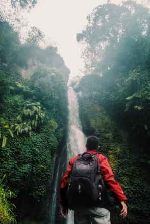 man wearing black backpack under waterfall