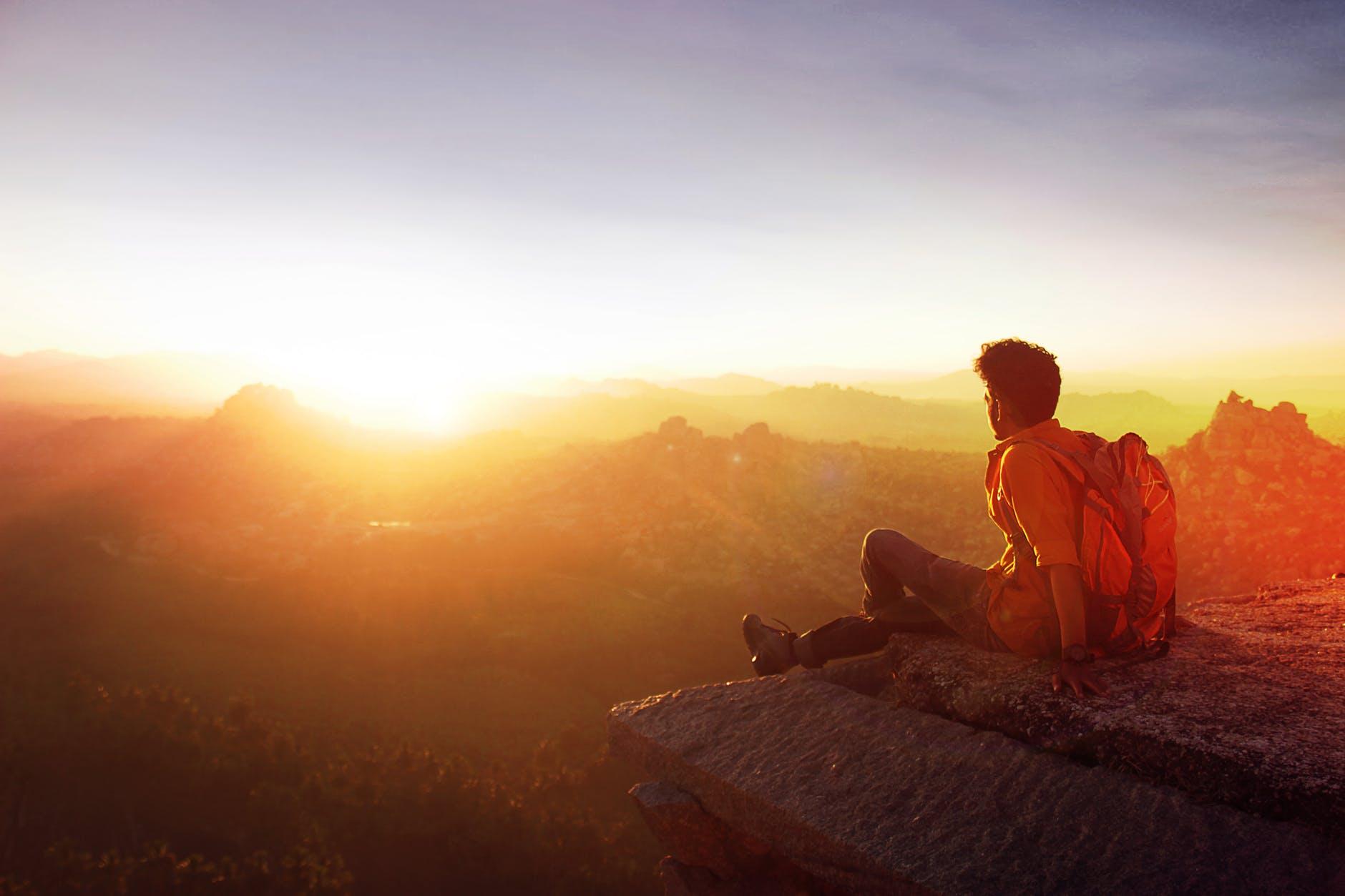man sitting on edge facing sunset