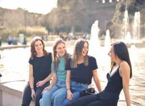 photo of women laughing while sitting near water fountain