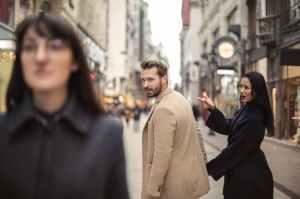 man in beige coat standing near woman in black coat